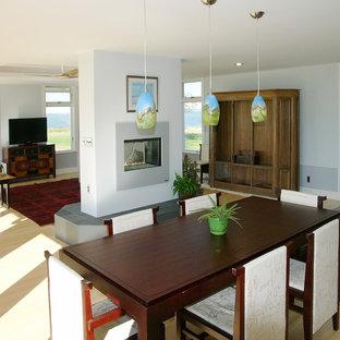 Cette photo montre une salle à manger ouverte sur la cuisine asiatique de taille moyenne avec un mur bleu, un sol en bambou, une cheminée double-face et un manteau de cheminée en métal.