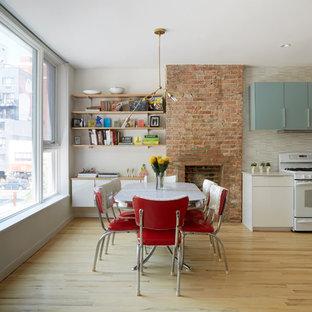 Ejemplo de comedor vintage con paredes beige, suelo de madera clara, chimenea tradicional y marco de chimenea de ladrillo
