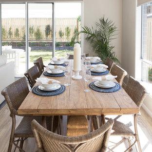 Idee per una sala da pranzo aperta verso il soggiorno costiera di medie dimensioni con pareti beige e pavimento in vinile