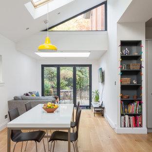 Modelo de comedor contemporáneo, abierto, con paredes blancas, suelo de madera clara y suelo azul