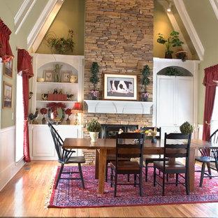 Große Country Wohnküche mit grüner Wandfarbe, hellem Holzboden, Kaminsims aus Stein und Hängekamin in Atlanta