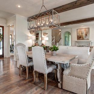 Immagine di una grande sala da pranzo aperta verso il soggiorno chic con pareti bianche, pavimento in legno massello medio e camino ad angolo
