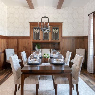 Example of a transitional medium tone wood floor and brown floor enclosed dining room design in Dallas with white walls