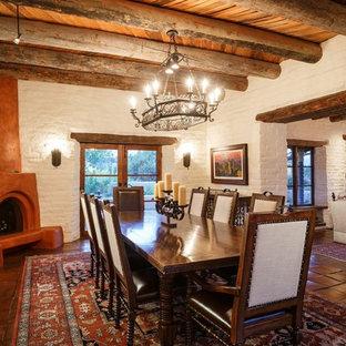 Idee per una grande sala da pranzo aperta verso il soggiorno stile americano con pareti bianche, pavimento in terracotta, camino ad angolo e cornice del camino in intonaco