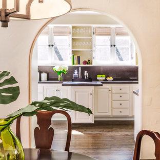 Idee per una sala da pranzo aperta verso la cucina mediterranea di medie dimensioni con pareti verdi, parquet scuro e nessun camino