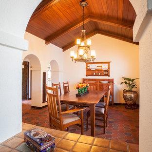 Cette photo montre une grande salle à manger méditerranéenne fermée avec un mur blanc, un sol en carreau de terre cuite et aucune cheminée.