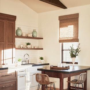Foto di una sala da pranzo aperta verso la cucina mediterranea di medie dimensioni con pareti beige, pavimento in terracotta e pavimento rosso