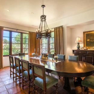 Cette image montre une salle à manger méditerranéenne avec un mur blanc, un sol en carreau de terre cuite, aucune cheminée et un sol orange.
