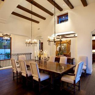 Medelhavsstil inredning av en mellanstor matplats med öppen planlösning, med vita väggar, mörkt trägolv, en hängande öppen spis och brunt golv