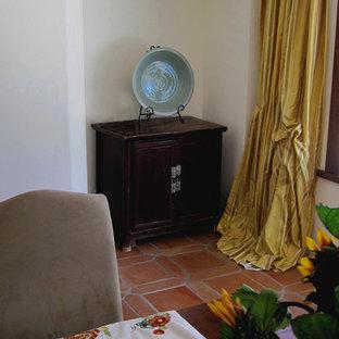 Foto di una piccola sala da pranzo aperta verso la cucina mediterranea con pareti bianche, pavimento in terracotta e pavimento rosso