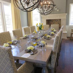 Esempio di una grande sala da pranzo american style con pareti grigie, pavimento in legno massello medio, camino classico e cornice del camino in legno