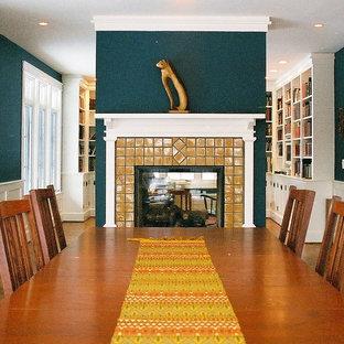 Modelo de comedor de estilo americano, de tamaño medio, cerrado, con paredes azules, suelo de madera oscura, chimenea de doble cara, marco de chimenea de baldosas y/o azulejos y suelo marrón