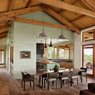 Immagine di un'ampia sala da pranzo aperta verso il soggiorno country con pavimento marrone, pareti verdi, parquet scuro, travi a vista, soffitto a volta, soffitto in legno e pareti in perlinato