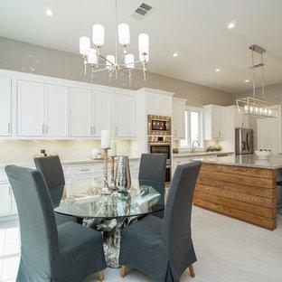 Idee per una sala da pranzo aperta verso la cucina chic con pareti beige, pavimento in ardesia e pavimento beige