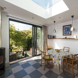 Immagine di una piccola sala da pranzo aperta verso il soggiorno contemporanea con pareti grigie, pavimento in laminato, stufa a legna e pavimento grigio