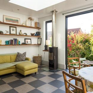 Foto di una piccola sala da pranzo aperta verso il soggiorno contemporanea con pareti grigie, pavimento in laminato, stufa a legna e pavimento grigio