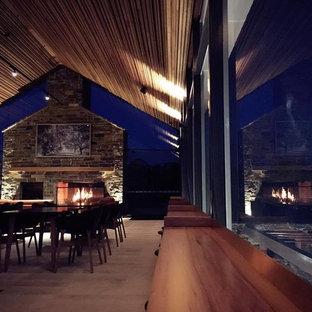 Ispirazione per una sala da pranzo design con pareti nere, pavimento in travertino e cornice del camino in pietra