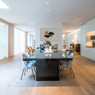 Design ideas for a contemporary dining room in London with white walls, medium hardwood flooring and brown floors.