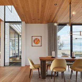 Aménagement d'une salle à manger ouverte sur le salon contemporaine avec un mur blanc, un sol en bois brun, aucune cheminée, un sol marron et un plafond en bois.