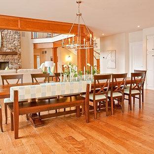 Стильный дизайн: большая гостиная-столовая в морском стиле с белыми стенами, паркетным полом среднего тона, стандартным камином и фасадом камина из камня - последний тренд