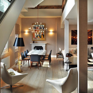 Medium sized contemporary open plan dining room in London with beige walls, a standard fireplace and light hardwood flooring.