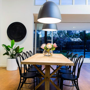 Contemporary dining room in Adelaide with white walls, medium hardwood floors and brown floor.