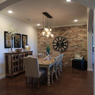 Idee per una sala da pranzo aperta verso la cucina tradizionale di medie dimensioni con pareti beige, pavimento in cemento, camino ad angolo e cornice del camino in mattoni