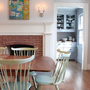 Idées déco pour une grand salle à manger classique fermée avec un mur gris, un sol en bois clair, une cheminée standard, un manteau de cheminée en brique et un sol marron.
