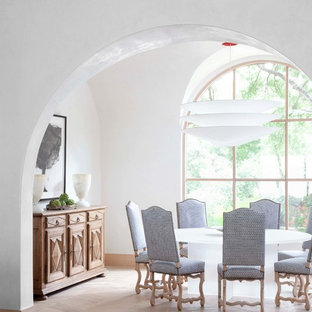 This is an example of a mediterranean dining room in Austin with white walls and medium hardwood flooring.