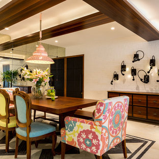 Design ideas for a mid-sized eclectic dining room in Mumbai with brown floor.