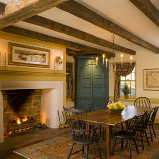 Example of a mid-sized mountain style dark wood floor enclosed dining room design in Philadelphia with beige walls, a standard fireplace and a plaster fireplace