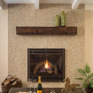 На фото: класса люкс кухни-столовые в средиземноморском стиле с бежевыми стенами, полом из керамогранита, подвесным камином, фасадом камина из кирпича и коричневым полом