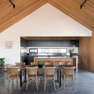 Cette image montre une salle à manger ouverte sur le salon rustique en bois avec un mur blanc, béton au sol, un sol gris, un plafond voûté et un plafond en bois.