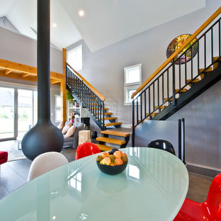 Example of a trendy dining room design in Vancouver with a hanging fireplace