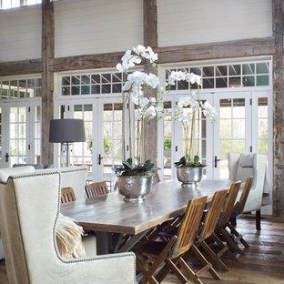 Cette image montre une grande salle à manger ouverte sur le salon rustique avec un mur blanc, un sol en bois brun, un sol marron et aucune cheminée.