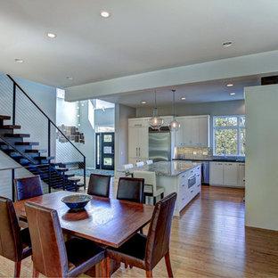 Idee per una grande sala da pranzo aperta verso la cucina minimal con pareti grigie, pavimento in bambù e nessun camino