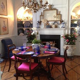 Idee per una sala da pranzo vittoriana chiusa e di medie dimensioni con pareti bianche, pavimento in legno massello medio, camino classico, cornice del camino in legno e pavimento marrone