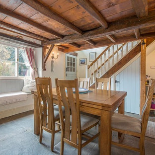 Small country enclosed dining room in Other with beige walls, slate flooring, a wood burning stove and a stone fireplace surround.