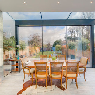 Design ideas for a contemporary enclosed dining room in London with multi-coloured walls and beige floors.