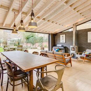 Immagine di una sala da pranzo aperta verso il soggiorno design con pareti grigie, parquet chiaro, stufa a legna, cornice del camino in metallo e pavimento beige