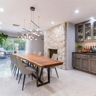 Foto de comedor de cocina clásico renovado, grande, con paredes grises, suelo de madera en tonos medios, chimeneas suspendidas, marco de chimenea de piedra y suelo marrón