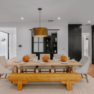 Example of a mid-sized country medium tone wood floor and brown floor great room design in Los Angeles with white walls