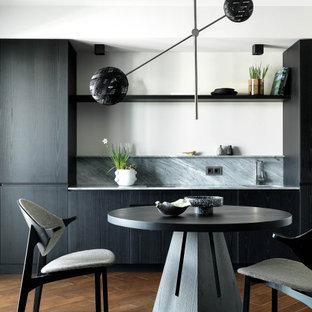 На фото: кухня-столовая в современном стиле с белыми стенами, темным паркетным полом и коричневым полом с