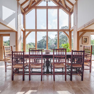 Photo of a large rustic open plan dining room in Other with white walls and grey floors.