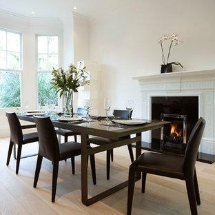 Idées déco pour une salle à manger victorienne avec un mur blanc, un sol en bois clair et une cheminée standard.