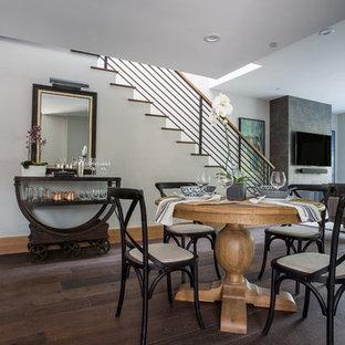 Foto di una piccola sala da pranzo aperta verso il soggiorno tradizionale con pareti grigie, parquet scuro, camino classico, cornice del camino in cemento e pavimento marrone