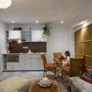 Esempio di una piccola sala da pranzo tropicale con pareti bianche e pavimento in laminato