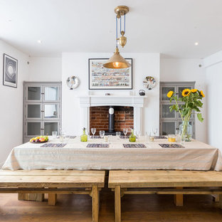 Photo of a classic dining room in London with white walls, medium hardwood flooring and a wood burning stove.