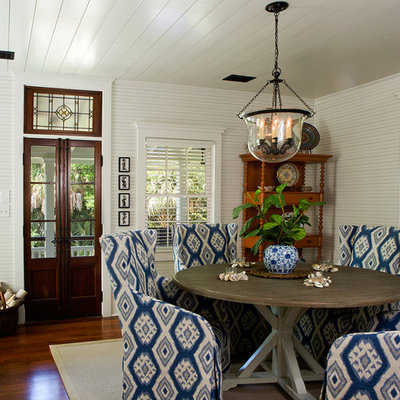 Example of a small beach style medium tone wood floor dining room design in Charleston with white walls