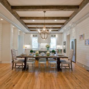 Elegant medium tone wood floor kitchen/dining room combo photo in Charleston with white walls